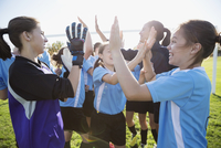 Middle school girl soccer team celebrating high fiving on field