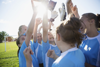middle school girl soccer team celebrating and cheering with trophy