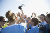 Exuberant middle school girl soccer team celebrating and cheering with trophy