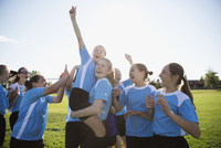 Exuberant middle school girl soccer team celebrating and cheering on field