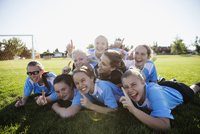 Portrait enthusiastic middle school girl soccer team celebrating and gesturing number one on field