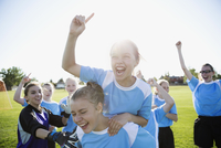 Exuberant middle school girl soccer team celebrating and cheering on sunny field