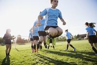 Middle school girl soccer team running drills at practice on sunny field 11096043580| 写真素材・ストックフォト・画像・イラスト素材|アマナイメージズ