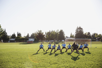 Coach and middle school girl soccer team stretching at practice on sunny field 11096043581| 写真素材・ストックフォト・画像・イラスト素材|アマナイメージズ