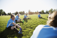 Middle school girl soccer team stretching at practice on sunny field 11096043584| 写真素材・ストックフォト・画像・イラスト素材|アマナイメージズ
