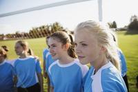 Middle school girl soccer team looking away on field