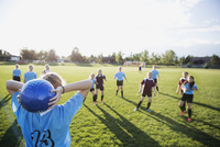 Middle school girl soccer team playing game on sunny field