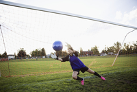 Middle school girl soccer goalie catching soccer ball at net