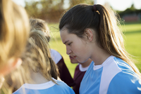Attentive middle school girl soccer player listening in huddle