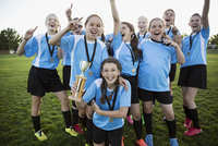 Portrait exuberant middle school girl soccer team celebrating and cheering with trophy