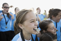 Enthusiastic middle school girl soccer player biting medal celebrating with teammates