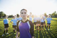Portrait confident middle school girl soccer goalie showing attitude with teammates on sunny field