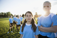 Portrait confident middle school girl soccer players showing attitude with teammates on sunny field