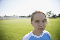 Portrait confident middle school girl soccer player on sunny field