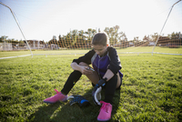 Middle school girl soccer goalie listening to music with headphones and mp3 player on sunny field