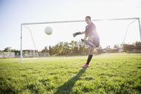 Middle school girl soccer goalie kicking the ball on sunny field 11096043662| 写真素材・ストックフォト・画像・イラスト素材|アマナイメージズ
