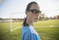 Portrait confident middle school girl soccer player wearing goggles on field 11096043664| 写真素材・ストックフォト・画像・イラスト素材|アマナイメージズ