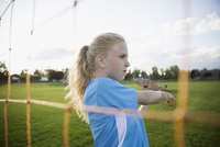 Serious middle school girl soccer player stretching at goal net