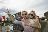 Portrait enthusiastic young couple piggybacking and gesturing at summer music festival entrance