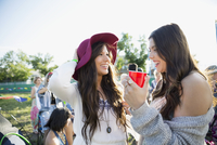 Young women drinking and hanging out at summer music festival campsite