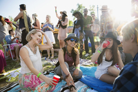 Young friends drinking and hanging out at summer music festival campsite