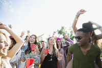 Young crowd drinking and dancing at summer music festival