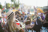 Young friends hanging out and drinking at summer music festival campsite 11096043990| 写真素材・ストックフォト・画像・イラスト素材|アマナイメージズ