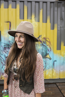 Portrait smiling brunette woman wearing hat looking away in front of graffiti wall