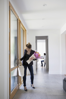 Businesswoman returning home with groceries and flowers in foyer
