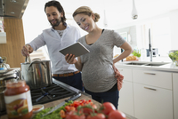 Pregnant couple with digital tablet cooking pasta sauce in kitchen
