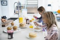 Sisters eating breakfast at kitchen island 11096044172| 写真素材・ストックフォト・画像・イラスト素材|アマナイメージズ