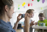 Mother with camera phone photographing baby son with birthday cake 11096044252| 写真素材・ストックフォト・画像・イラスト素材|アマナイメージズ
