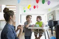 Mother watching sons eating birthday cake 11096044253| 写真素材・ストックフォト・画像・イラスト素材|アマナイメージズ