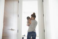 Mother holding baby son in doorway