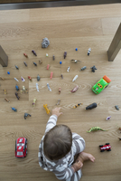 View from above baby boy playing with toys on hardwood floor