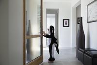 Boy in killer whale costume opening front door in foyer 11096044280| 写真素材・ストックフォト・画像・イラスト素材|アマナイメージズ