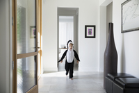 Boy in killer whale costume running through foyer