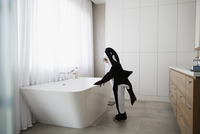 Boy in killer whale costume standing at bathtub in bathroom