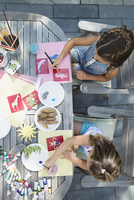 Girls painting at patio table