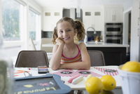 Portrait smiling girl making lemonade sign at dining table