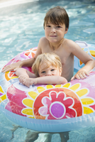 Portrait smiling boys inside inflatable ring in swimming pool