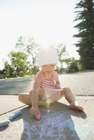 Girl drawing with sidewalk chalk on sunny sidewalk