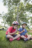 Boys wearing bike helmets blowing dandelions in grass at park 11096044488| 写真素材・ストックフォト・画像・イラスト素材|アマナイメージズ