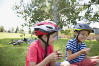 Boys wearing bike helmets blowing dandelions in grass at park 11096044490| 写真素材・ストックフォト・画像・イラスト素材|アマナイメージズ