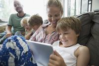 Family relaxing using digital tablet on living room sofa 11096044497| 写真素材・ストックフォト・画像・イラスト素材|アマナイメージズ