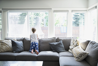 Curious boy in pajamas on sofa looking out living room window
