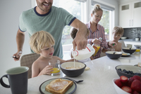 Father pouring milk into cereal for son at breakfast 11096044513| 写真素材・ストックフォト・画像・イラスト素材|アマナイメージズ