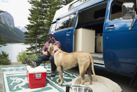 Man and dog relaxing outside camper van at remote lakeside