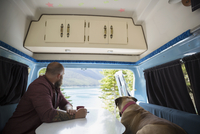 Man and dog sitting at table in the back of camper van at lakeside