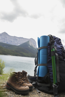 Hiking boots, walking poles, mat and backpack hiking equipment at lakeside
